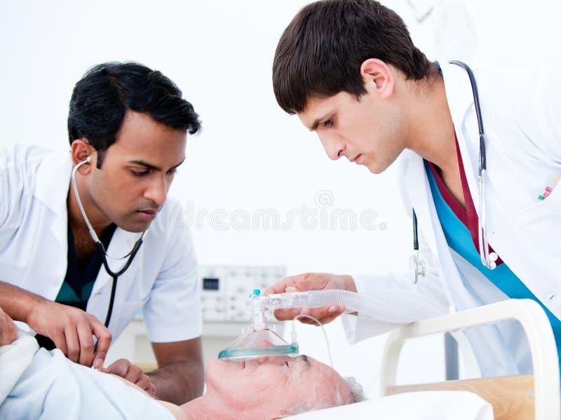 Médecins charismatiques réanimant un patient photo stock