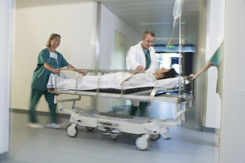 Médecins déplaçant le patient sur le chariot d'hôpital par le couloir d'hôpital image stock