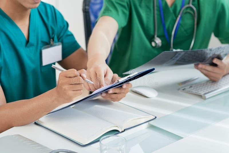Médecins de culture faisant des notes dans les disques médicaux photos libres de droits