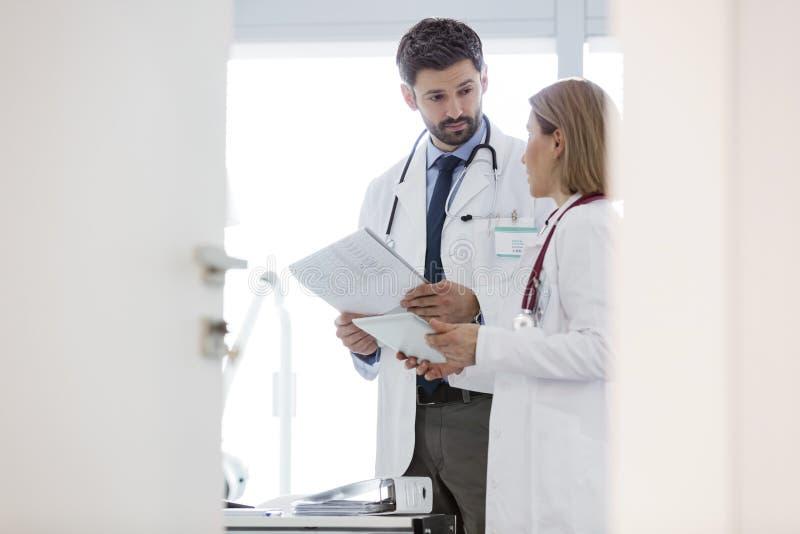 Médecins discutant au-dessus des disques médicaux au bureau dans l'hôpital photo libre de droits