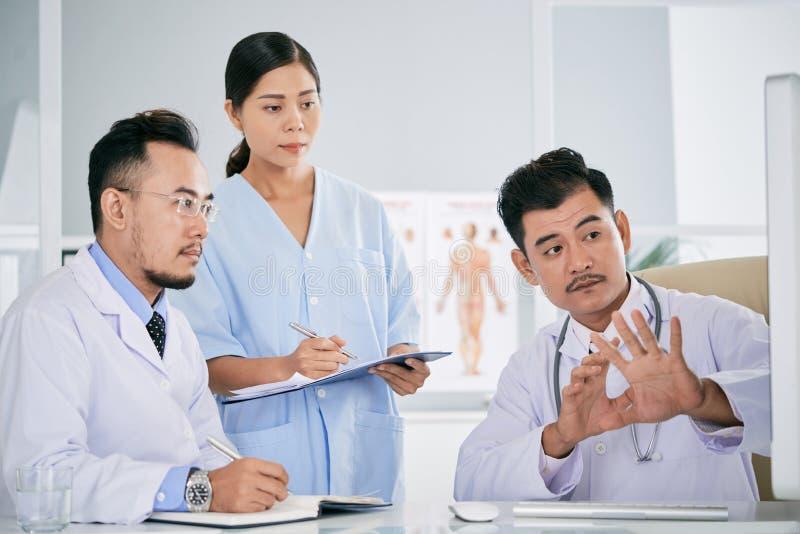 Médecins discutant le café difficile photos stock