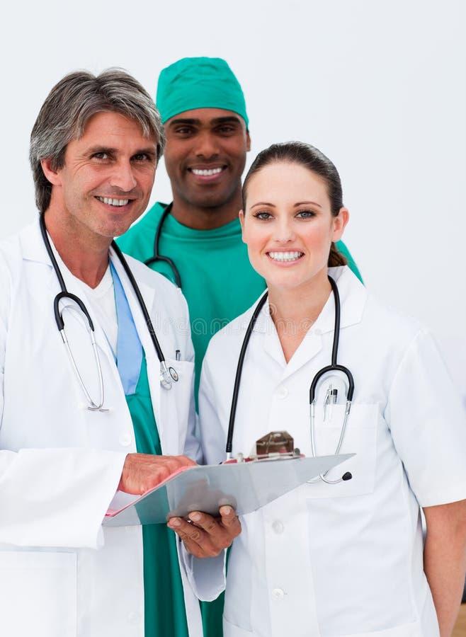 Médecins et chirurgien de sourire prenant des notes images stock