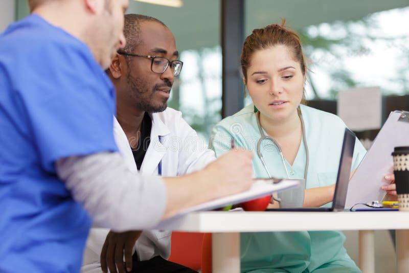 Médecins et infirmière ayant la réunion informelle dans la cantine d'hôpital photos libres de droits