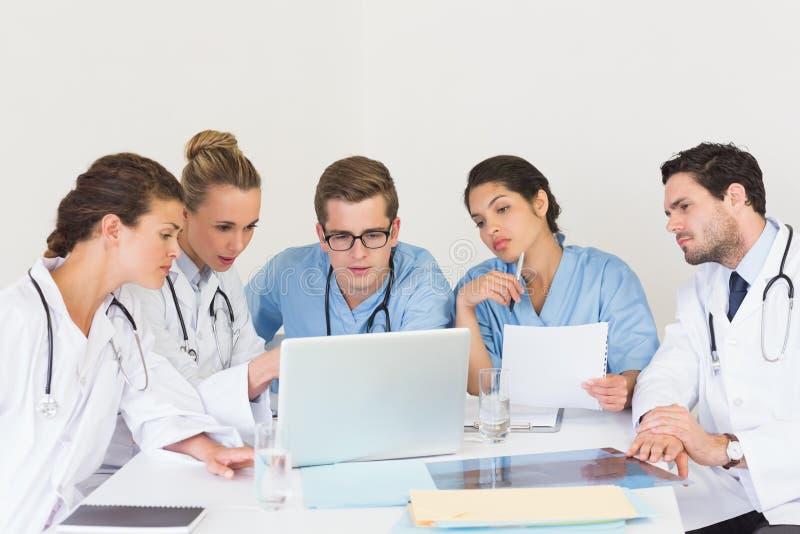 Médecins et infirmières discutant au-dessus de l'ordinateur portable image libre de droits