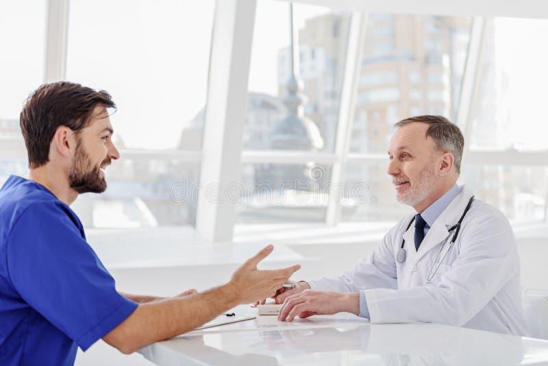 Médecins généralistes joyeux discutant leur travail photos stock