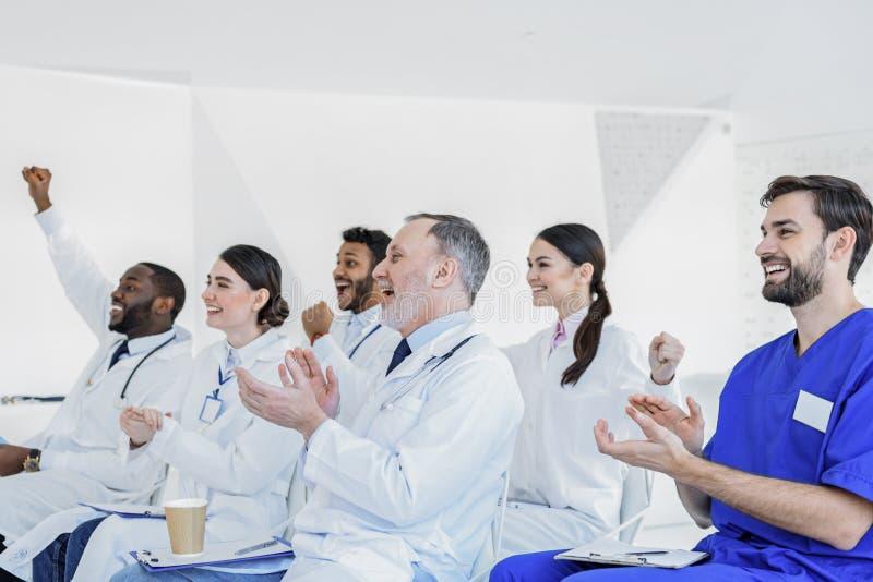 Médecins heureux battant des mains sur le séminaire photos stock