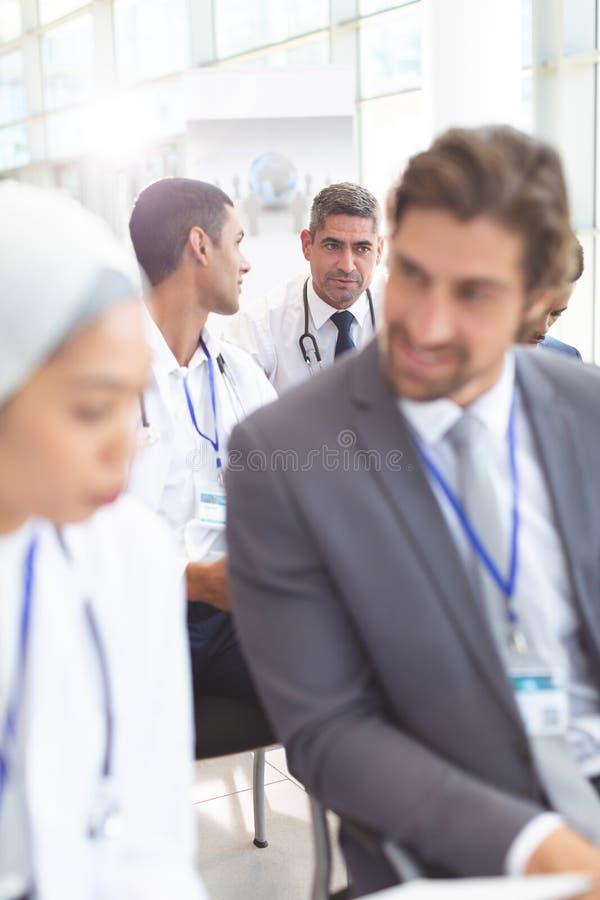Médecins masculins agissant l'un sur l'autre les uns avec les autres pendant le séminaire images stock