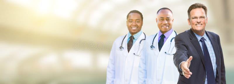 Médecins masculins caucasiens d'homme d'affaires et d'Afro-américain, infirmières image libre de droits