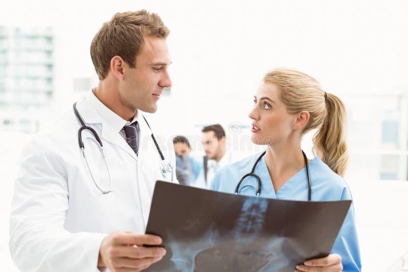 Médecins masculins et féminins examinant le rayon X photos stock