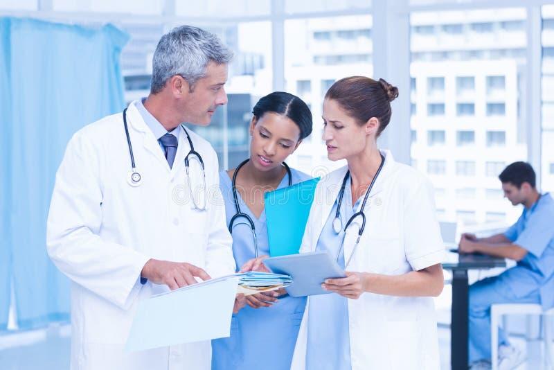 Médecins masculins et féminins travaillant sur des rapports photo stock