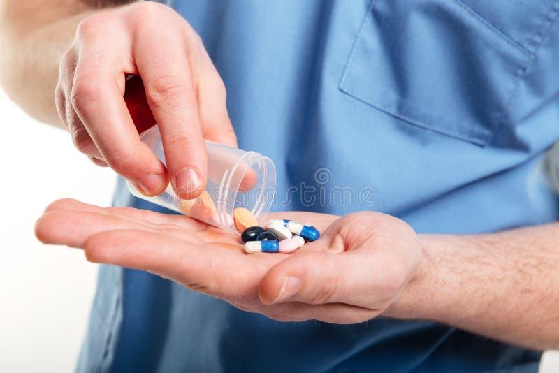 Médecins masculins versant le froma de pilules une bouteille sur sa paume photos stock