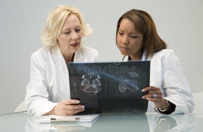 Médecins regardant le rayon de x images stock