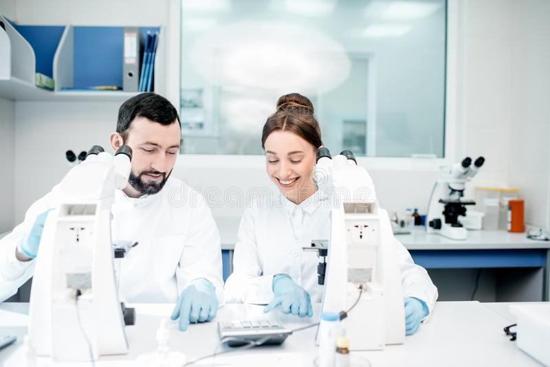 Médecins travaillant avec le microscope au laboratoire photographie stock