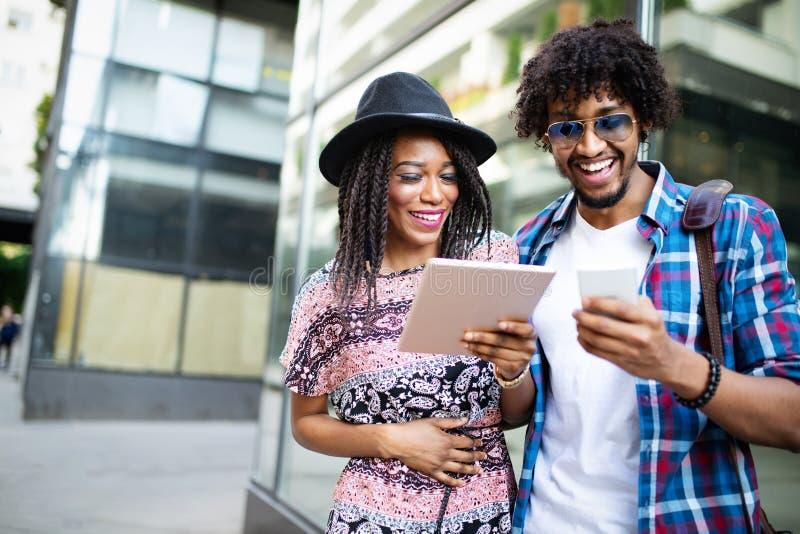 Médias de observation de couples noirs heureux dans une table numérique extérieure photo stock