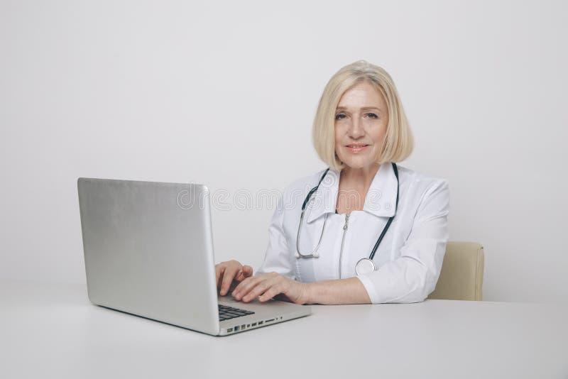 Médica em gabinete sentada à mesa em casaco médico com computador imagem de stock