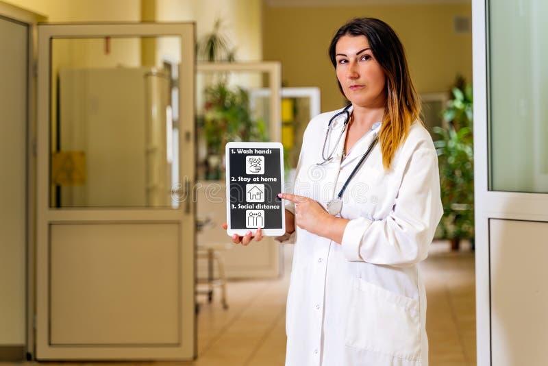 Médica em pé num corredor hospitalar com ícones e texto para prevenção de comprimidos e coronavírus imagem de stock