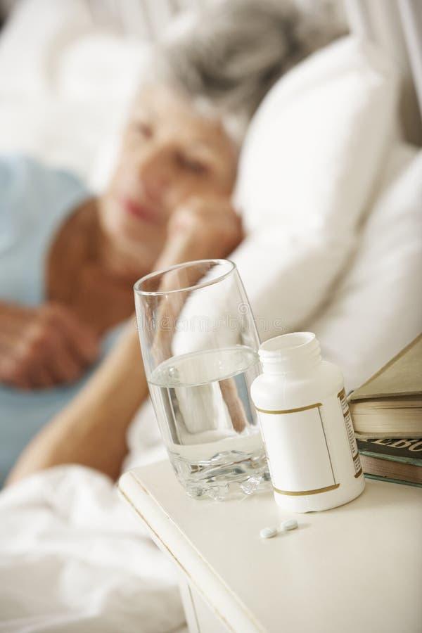 Médicament sur la table de chevet de la femme supérieure de sommeil photographie stock libre de droits