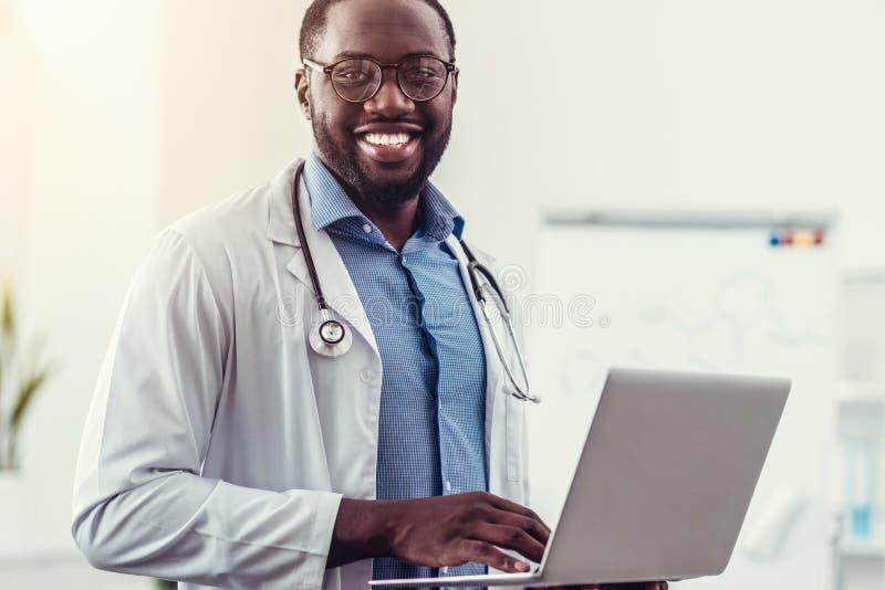 Médico afroamericano alegre que presenta con el ordenador portátil en manos foto de archivo