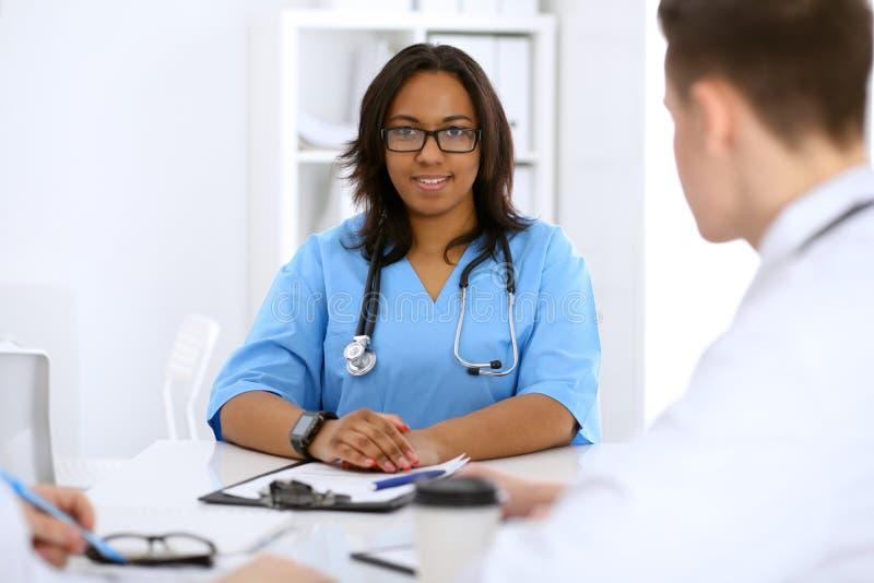 Médico afroamericano de sexo femenino con los colegas en fondo en el hospital Concepto de la medicina y de la atención sanitaria foto de archivo libre de regalías