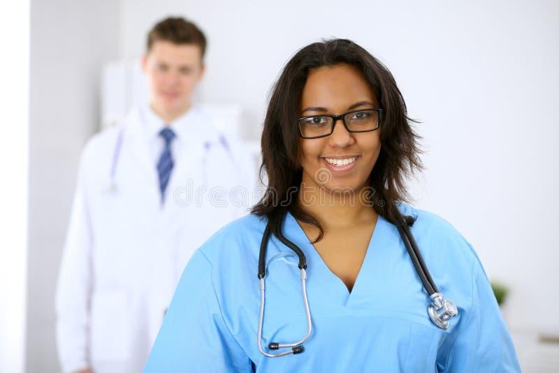 Médico afroamericano de sexo femenino con los colegas en fondo en el hospital Concepto de la medicina y de la atención sanitaria imagen de archivo