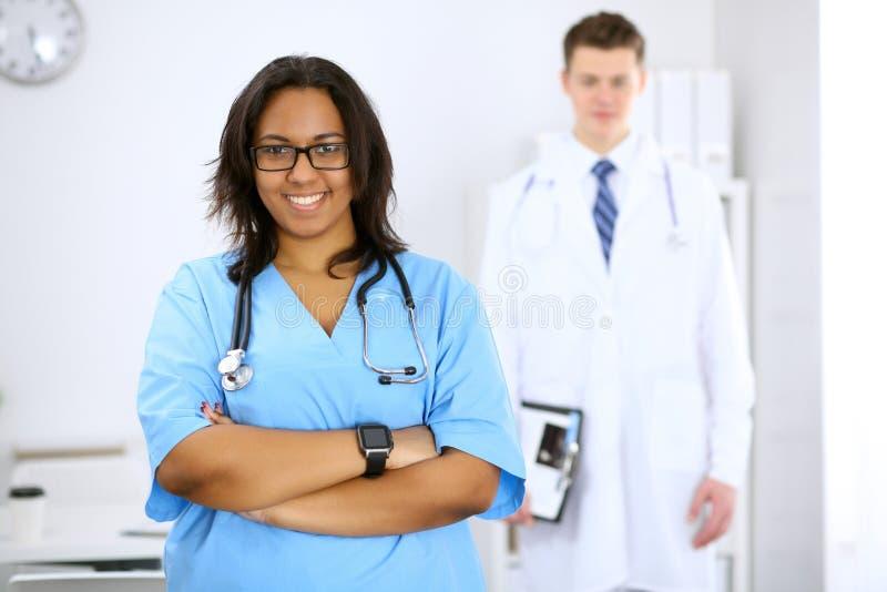 Médico afroamericano de sexo femenino con los colegas en fondo en el hospital Concepto de la medicina y de la atención sanitaria foto de archivo
