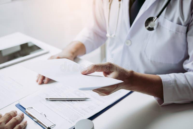 Médico asiático a falar numa sala clínica e a entregar uma receita ao doente imagem de stock