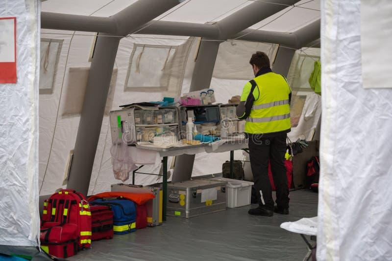 Médico Check para los suministros médicos dentro de la tienda temporal del centro de control de rescate fotografía de archivo