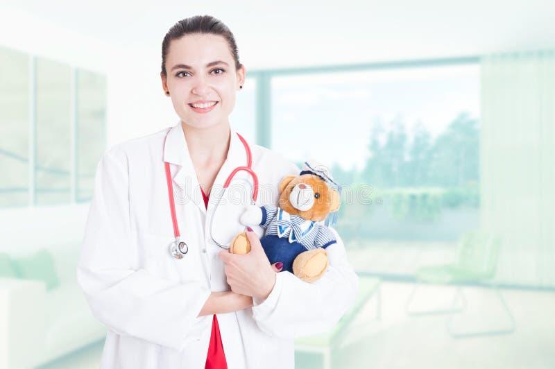 Médico da mulher profissional que guarda o urso de peluche imagens de stock