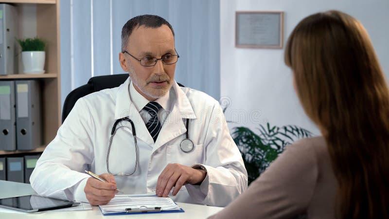 Médico de cabecera que escucha el paciente, completando seguro médico, atención sanitaria fotos de archivo libres de regalías
