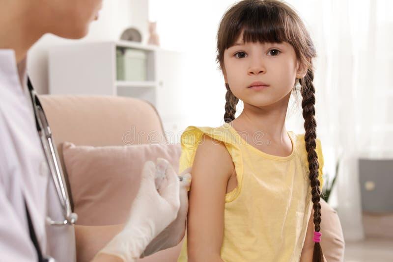 M?dico de cabecera que vacuna al peque?o ni?o fotografía de archivo libre de regalías