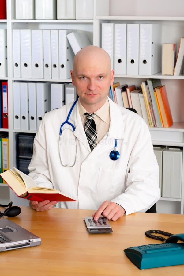 Médico de família amigável novo com a calculadora do livro e de bolso foto de stock