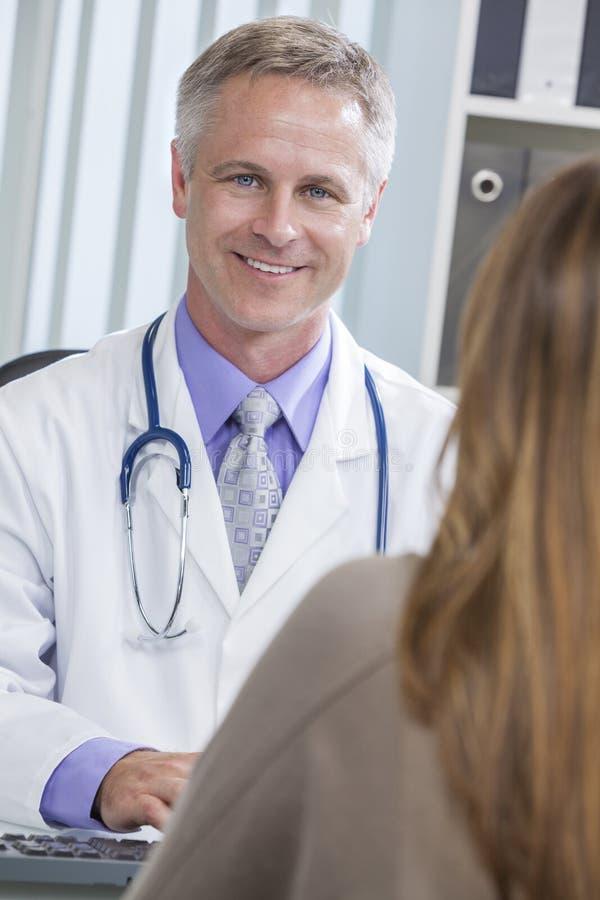 Médico de hospital de sexo masculino que habla con el paciente femenino imagen de archivo
