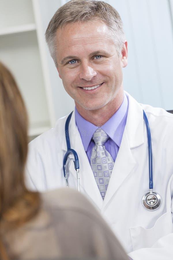 Médico de hospital de sexo masculino que habla con el paciente femenino fotos de archivo