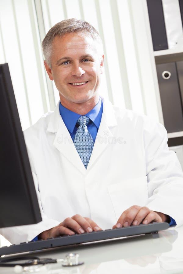 Médico de hospital de sexo masculino que usa el ordenador imagen de archivo
