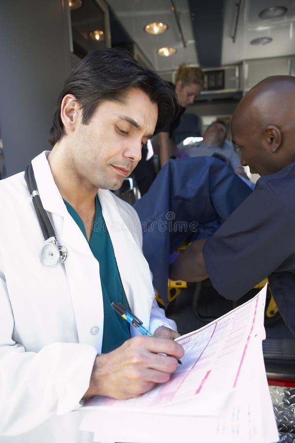 Médico de hospital que toma a paramédicos de las notas imagen de archivo