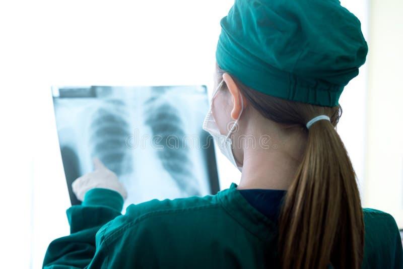 Médico de las mujeres femeninas que mira radiografías en un hospital comprobación de la película del rayo del pecho x en la sala fotos de archivo