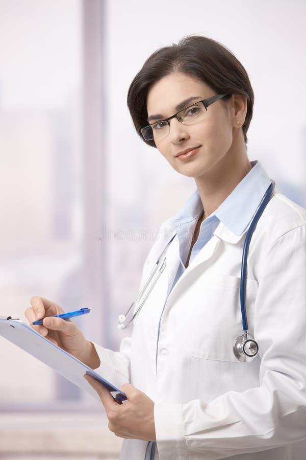 Médico de sexo femenino que hace papeleo en hospital fotos de archivo libres de regalías