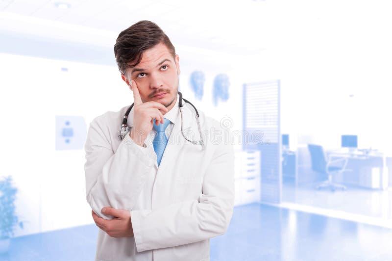 Médico de sexo masculino joven que piensa mientras que mira distancia imagenes de archivo