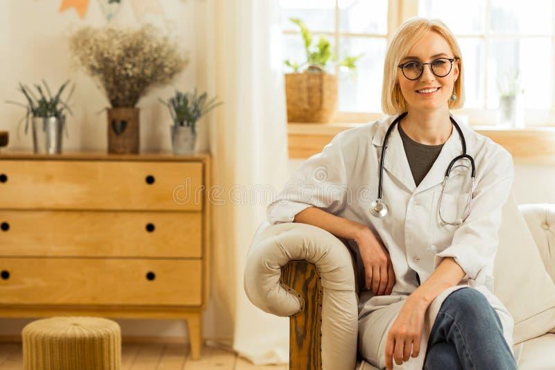 Médico de sorriso em um revestimento branco que senta-se no sofá foto de stock