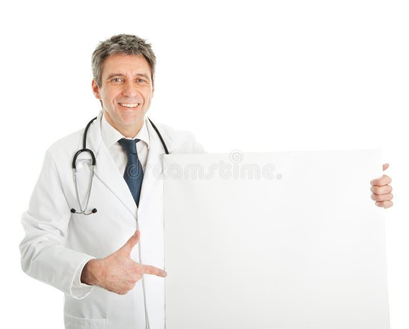 Médico de sorriso que apresenta a placa vazia foto de stock royalty free