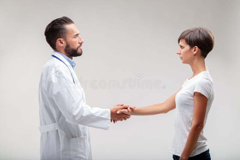 Médico dedicado e paciente que agitam as mãos fotos de stock royalty free