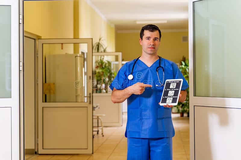 Médico do sexo masculino internado com comprimido e apontando para o mesmo ícones de prevenção do coronavírus imagem de stock