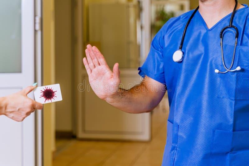 Médico do sexo masculino no corredor hospitalar, mostrando paragem com palma para doença de propagação do coronavírus foto de stock