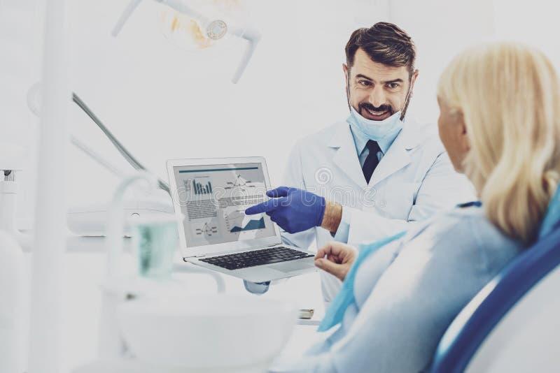 Médico encantado positivo que habla con su visitante foto de archivo libre de regalías