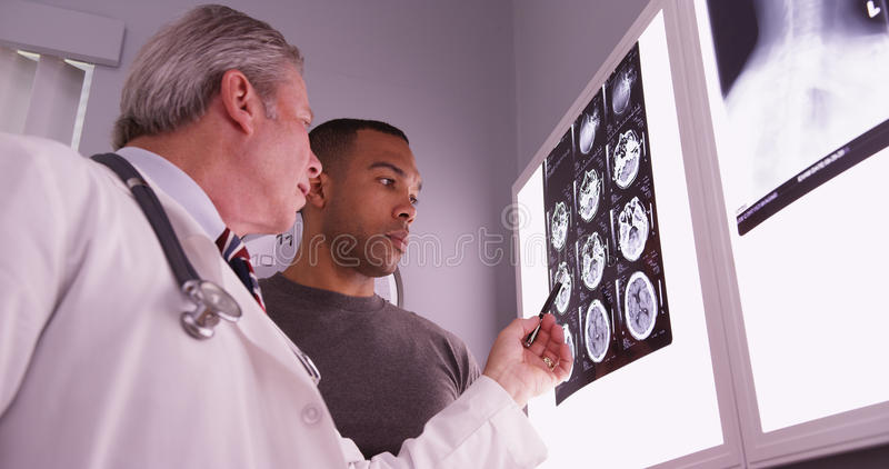 Médico envelhecido meados de que revê o raio de x do paciente africano imagens de stock royalty free
