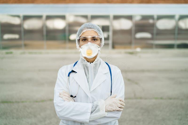 Médico equipado que espera a los pacientes que se encuentran frente a un centro médico de aislamiento Médico de Coronavirus COVID imagenes de archivo