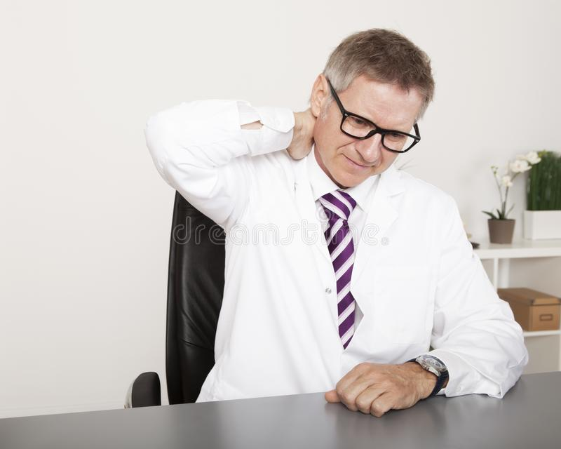 Médico esgotado Holding Back Neck fotografia de stock