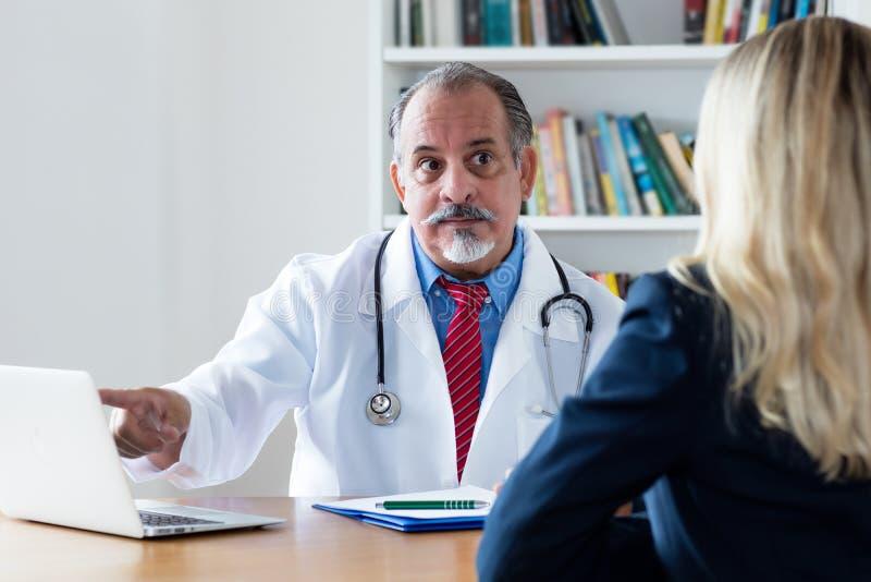 Médico geral que explica o diagnóstico ao paciente fêmea fotografia de stock royalty free