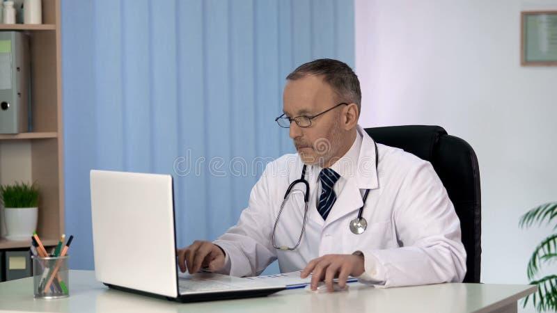 Médico geral que põe dados pacientes no informe médico eletrônico sobre o portátil fotografia de stock