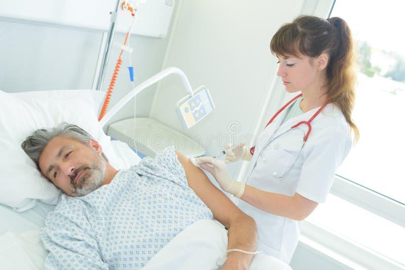 Médico a injetar o doente deitado na cama imagens de stock royalty free